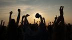 Viele zur Luft gestreckte Hände vor Sonnenuntergang