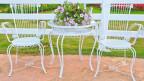 Weisse Gartenstühle und Gartentisch aus Metall.