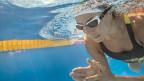 Frau schwimmt unter Wasser.