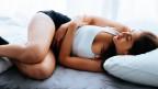 Frau krank im Bett, vermutlich ist ihr übel