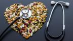 Hülsenfrüchte zu Herz drappiert daneben ein Stetoskop