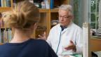 Arzt spricht mit Patientin, beide sitzen sich am Schreibtisch gegenüber