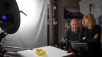 Ursula Nairn steht mit einem Kollegen im Fotostudio.