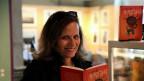 Frau mit Buch in der Hand blickt in die Kamera