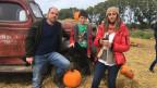 Christof Marti steht mit seinem Sohn und seiner Frau auf einem Kürbisfeld.