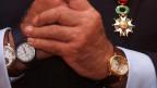 Mehrere Uhren an zwei Handgelenken