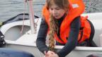 Kaori Krammer mit einer Schwimmweste auf einem Segelboot.
