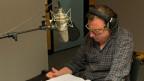 Beat Schlatter sitzt vor dem Mikrofon im Hörspielstudio und spricht seine Rolle.