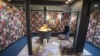 Der Waschbereich einer Toilette mit Blumentapete