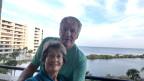 Reto Badraun mit seiner Frau Ruth auf dem Balkon. Im Hintergrund das Meer.