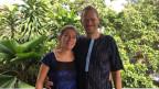 Cornelia und Peter Flückiger stehen auf einer Terrasse im Hintergrund sind Palmen.