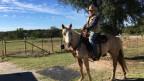 Mike Kägi mit Cowboyhut sitzend auf seinem Pferd.