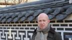 Daniel Faller steht vor einer verzierten koreanischen Mauer.