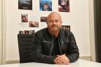Frank Lorenz, in schwarzer Lederjacke und rotem Bart, sitzt an einem Pult.