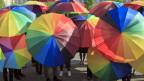Viele Schirme in den Regenbogenfarben sieht man auf einem Platz.