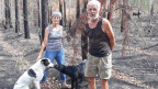 Heid und Hans stehen mit ihren zwei Hunden im ausgebrannten Waldstück.