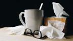 Bouillontasse mit verschneuzten Taschentüchern