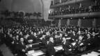 Männer in Anzug und Krawatte treffen sich in einem grossen Saal zur ersten Sitzung des Völkerbunds 1920 in Genf.