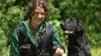 Melanie Müller kniend mit ihrem schwarzen Hund