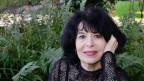 Frau mit schwarzen Haaren blickt in die Kamera