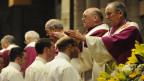 Junge Männer werden von Bischöfen zum Priester geweiht.