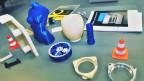 Ein Warndreieck, ein Räderwerk, eine Fassung und ein Frauentorso in blauer Farbe.