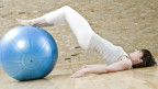 Frau turnt mit Gymnastikball.
