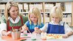 Eine Lehrerin betreut Kinder beim Bilder malen.