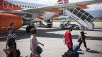 Blick auf eine Rollfeld mit Flugzeugen und Passagieren