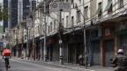 Ein Velokurier fährt durch eine leergefegte Strasse in Brasilien