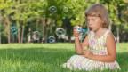 Ein Mädchen bläst Seifenblasen.