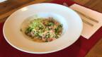 In einem weissen Teller hat es Pasta-Risotto mit Speck und Erbsen.