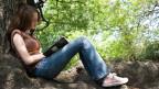 Eine Frau unter einem Baum schreibt in ihr Tagebuch.