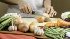Eine Mischung aus Gemüse, darunter Rüebli, Bohnen und Zwiebeln, wird auf einem Rüstbrett geschnitten.
