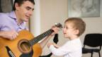 Ein Vater spielt mit seinem Sohn Gitarre und singt.