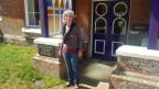 Anja St. Clair-Jones steht vor ihrem Haus. Sie trägt Jeans und Pullover.