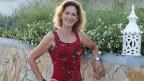 Claudine Halbheer steht in einem rot geblümten Kleid an einer Mauer.