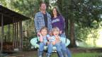 Familie Mann auf ihrem Grundstück, Beide Söhne sitzen auf der Schaukel.