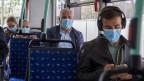 Leute sitzen mit Maske im Bus.