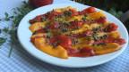 Geschmorte Peperoni mit Kapern garniert auf einem weissen Teller.