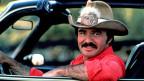"""Burt Reynolds in """"Smokey and The Bandit"""" in einer rasanten Autojagd und viel Countrymusik."""