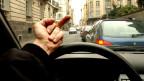 Ein Mann hält den Mittelfinger an eine Autoscheibe.