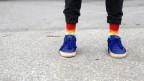 Männerbeine mit Socken in Regenbogenfarben.