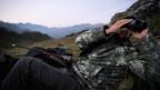 Ein Jäger blickt durch sein Fernglas während der Ansitz-Jagd auf Hirsche, auf der Alp Flix in Surses.