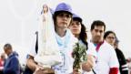 Pilgerinnen in Fatima halten eine Marienstatue.