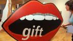 Ein roter Comicmund mit einem Aufrduck des englischen Wortes «gift» - «Geschenk»