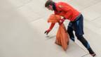 Ein Mann sammelt Abfall auf.
