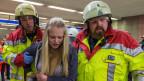 Zwei Feuerwehrmänner stützen eine junge Frau beim Gehen