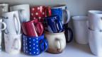 Ein Geschirrschrank mit bunten Tassen