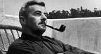 William Faulkner raucht Pfeife auf einem Balkon, schwarz-weiss Aufnahme.